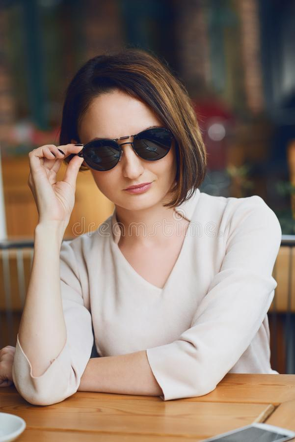 Young woman drinks coffee in cafeteria and posing with sunglasses stock images