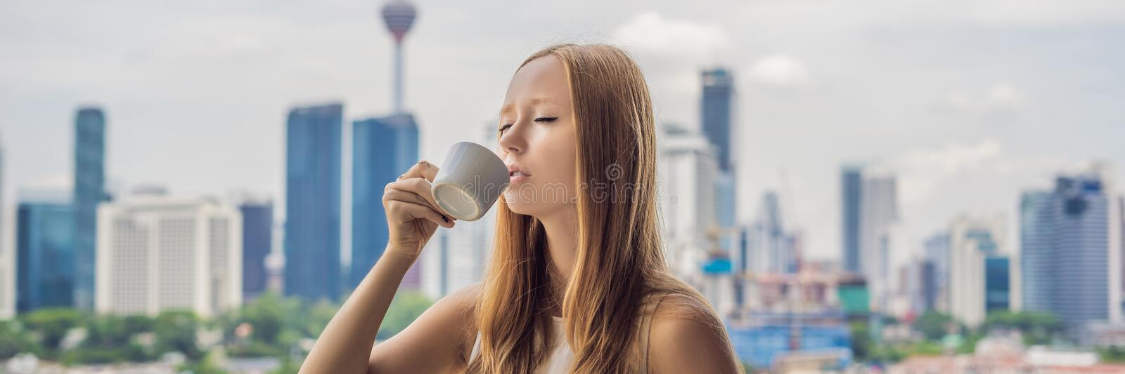Young woman drinks coffee in the morning on the balcony overlooking the big city and skyscrapers BANNER long format. Young woman drinks coffee in the morning on royalty free stock photos
