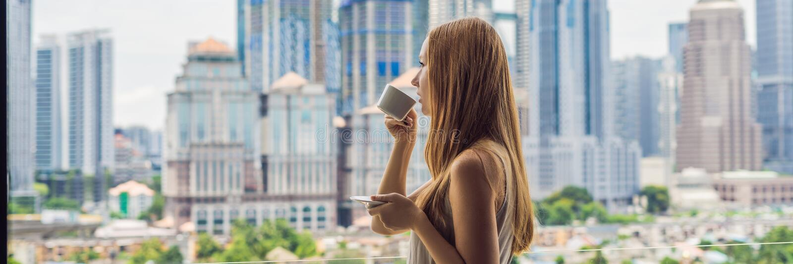 Young woman drinks coffee in the morning on the balcony overlooking the big city and skyscrapers BANNER long format royalty free stock photos