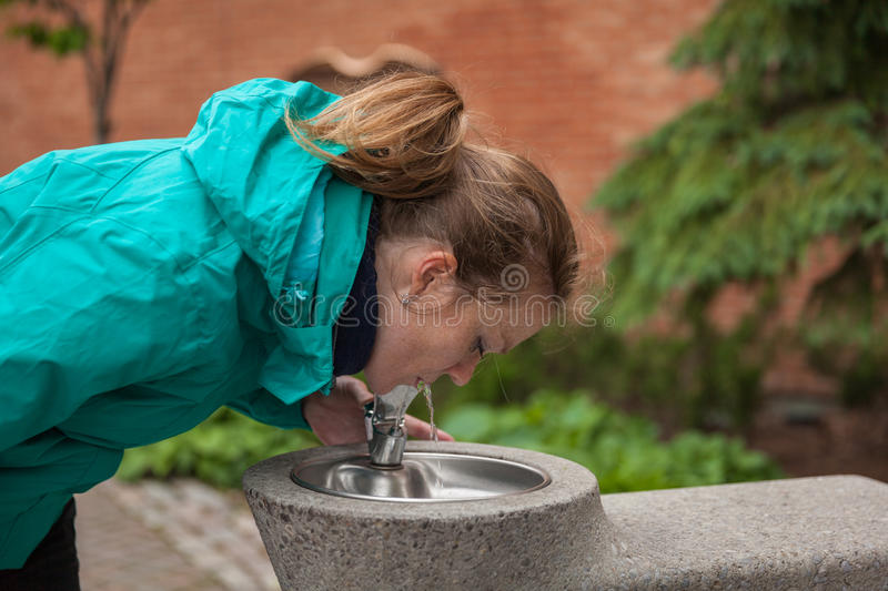 Young woman drinks water from drinking fountains. On the square in town stock photos