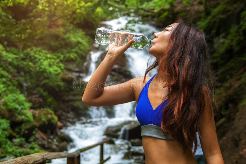 Young woman drinks water on a waterfall background. Sports asian girl drinks water from a bottle on the background of a waterfall stock photography