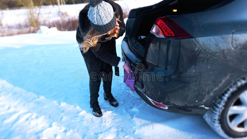 Young woman, driver, dry wiping her car with microfiber rag after washing it. Cleaning auto stock photography