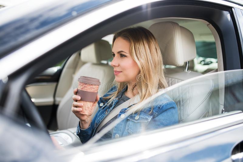 Young woman driver sitting in car, drinking coffee. royalty free stock photo