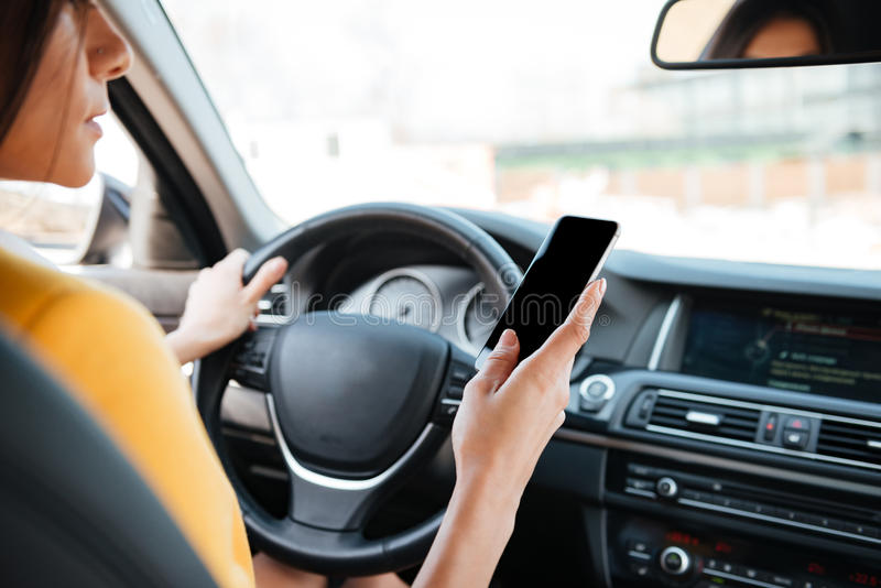 Young woman driver using touch screen smartphone royalty free stock images