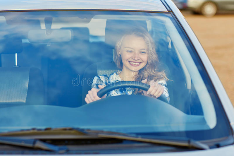 Young woman driving a car. Beautiful and confident young woman driving a car stock photos