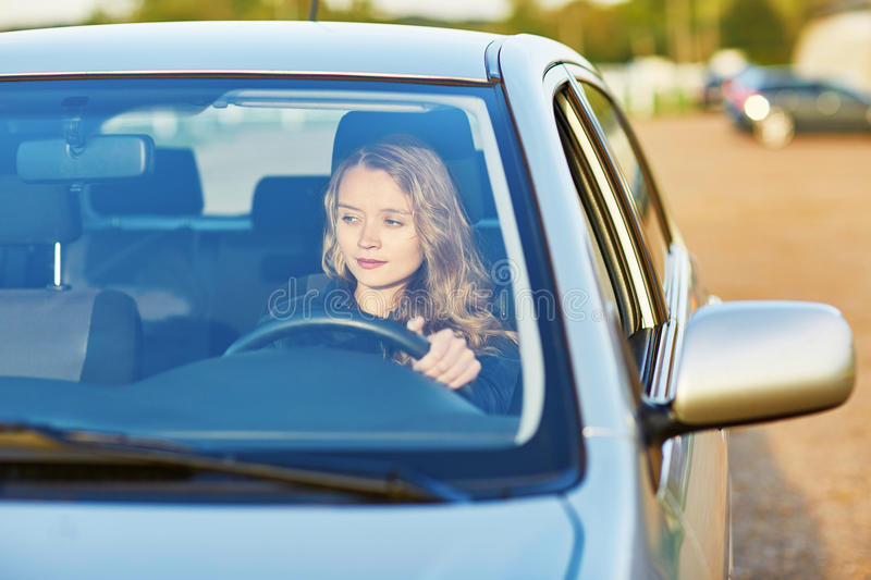 Young woman driving a car. Beautiful and confident young woman driving a car stock images