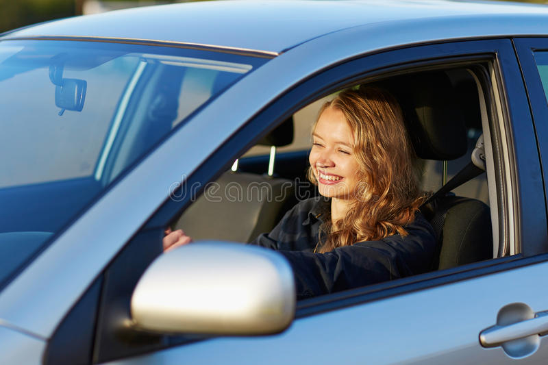 Young woman driving a car. Beautiful and confident young woman driving a car stock image
