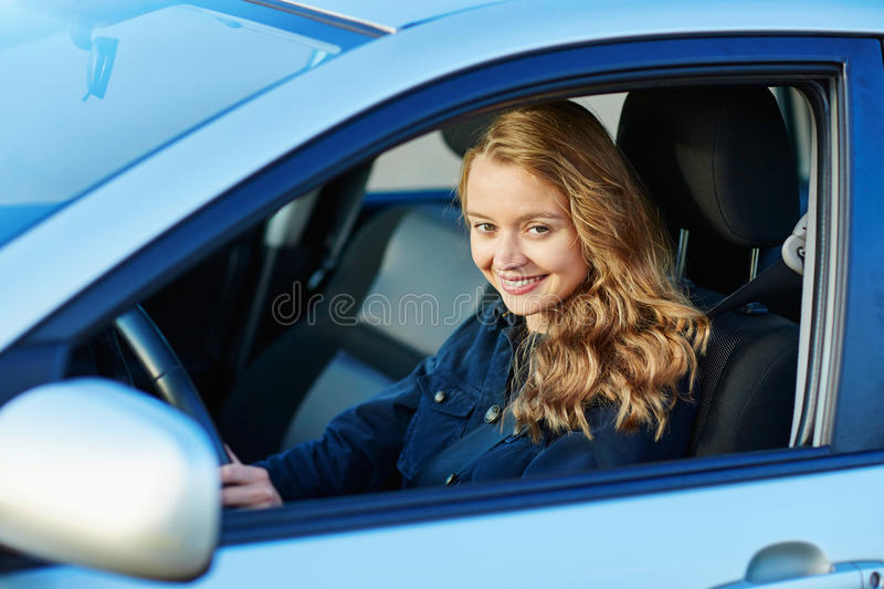 Young woman driving a car. Beautiful and confident young woman driving a car royalty free stock image