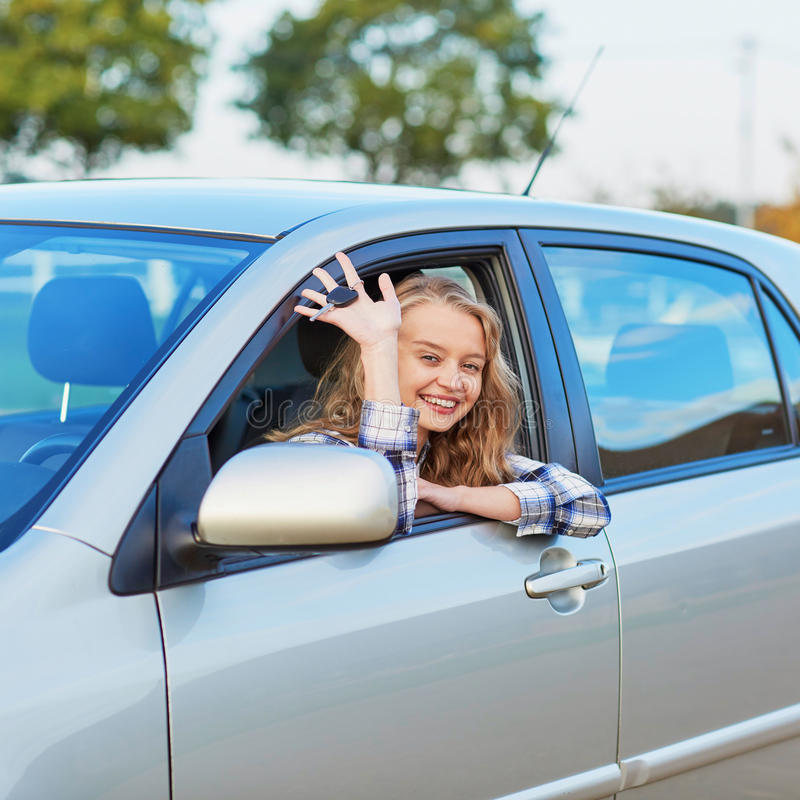 Young woman driving a car. Beautiful young confident woman driving a car stock photo