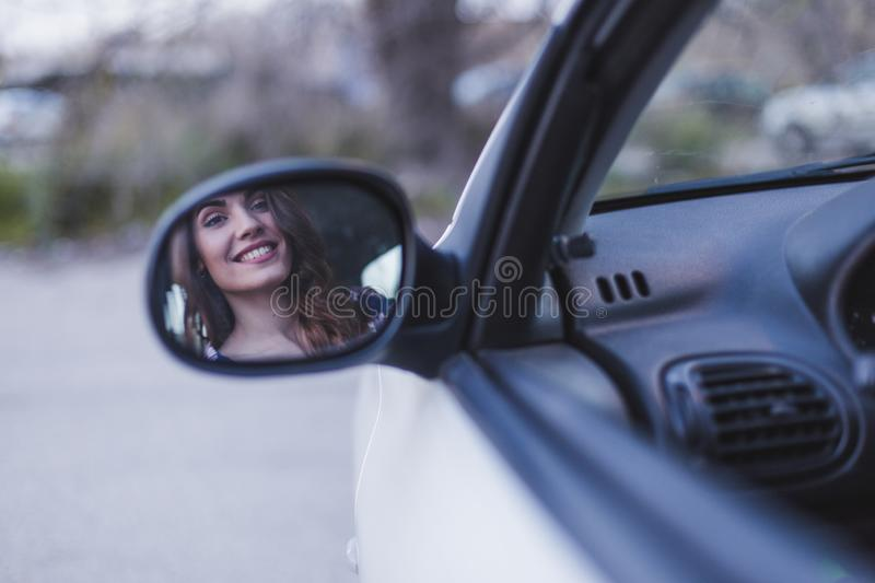 Young woman driving a car in the city. Portrait of a beautiful woman in a car, looking out of the window and smiling. Reflection. In rear mirror. Travel and stock photos