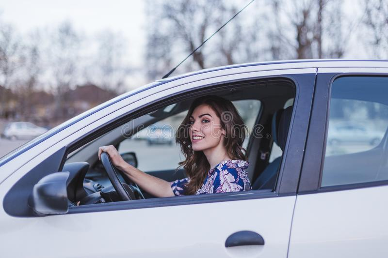 Young woman driving a car in the city. Portrait of a beautiful woman in a car, looking out of the window and smiling. Travel and stock photos