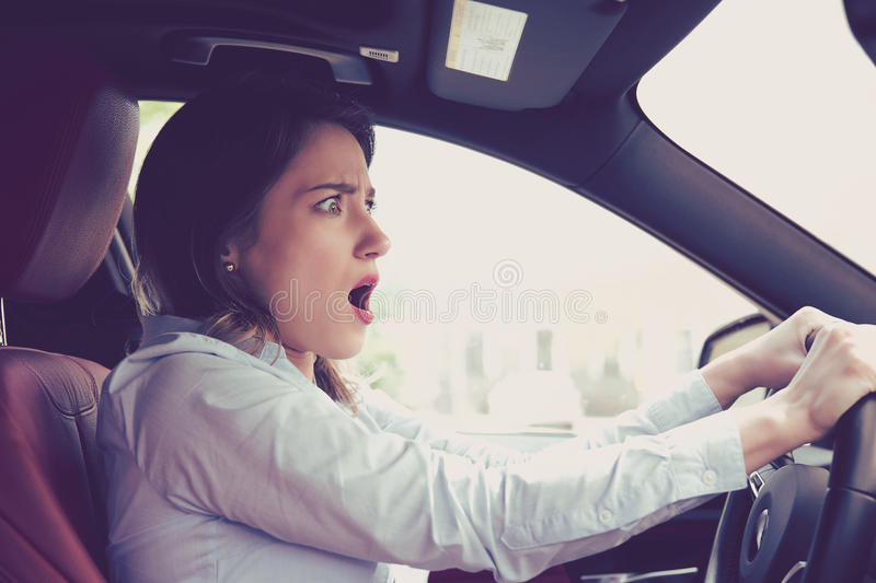 Young woman driving a car shocked about to have traffic accident royalty free stock photo