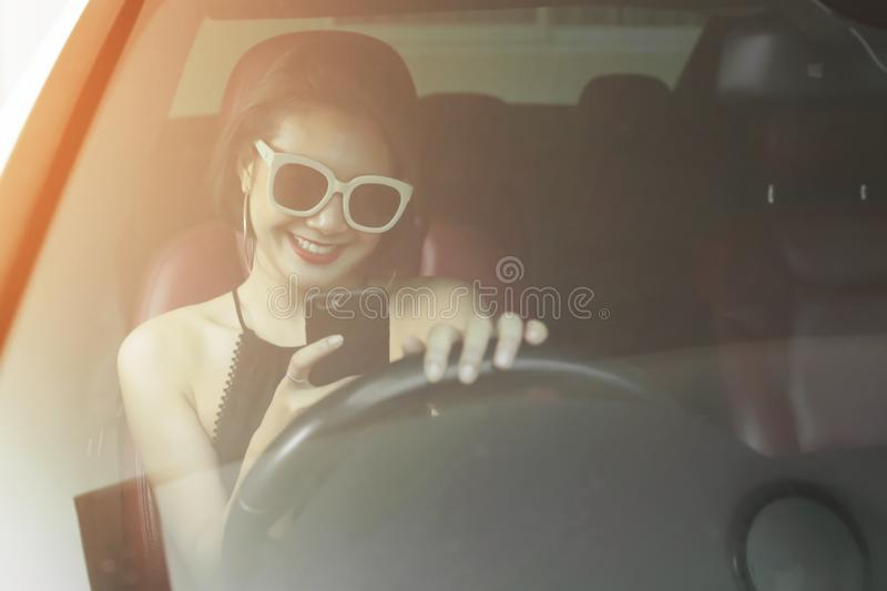 Young woman driving the car and talking phone on the road royalty free stock photography