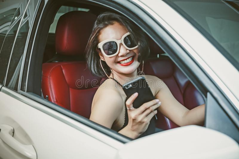 Young woman driving the car and talking phone on the road royalty free stock image