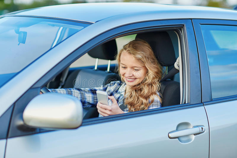 Young woman driving a car and using phone. Young woman using her smartphone while driving a car stock images