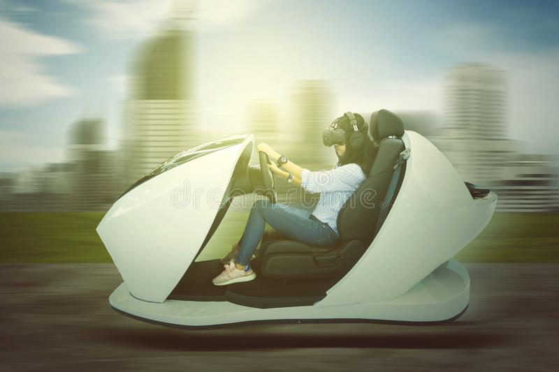 Young woman driving a futuristic car on the road royalty free stock photo