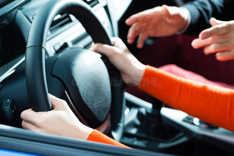 Young woman at driving lesson. Driving School - Young women steer a car with the steering wheel, maybe she has a driving test perhaps she exercises the parking stock photography