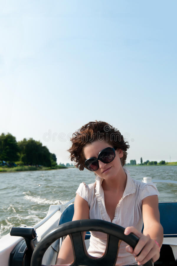 Young woman driving a motorboat stock photo