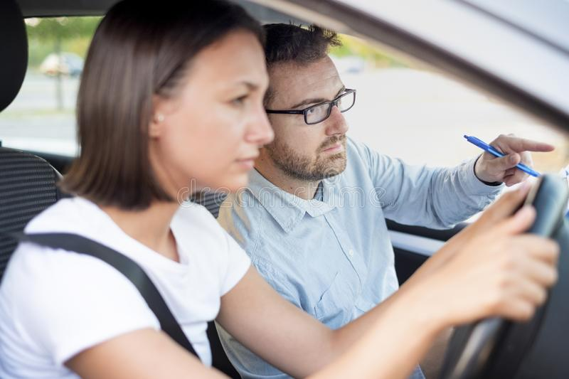 Young woman on a driving test with her instructor. Learning to drive a car. Driving school,main focus on the instructor royalty free stock photo