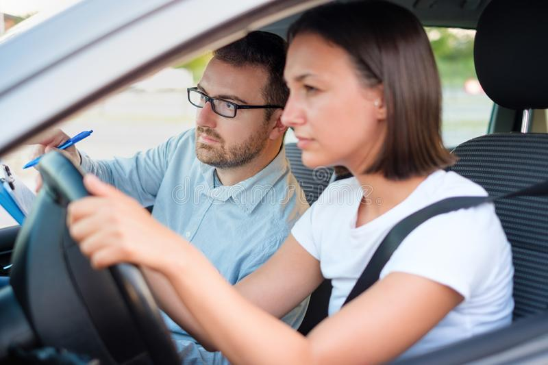 Learning to drive a car. Driving school. Young women on a driving test with her instructor, main focus on the instructor stock image