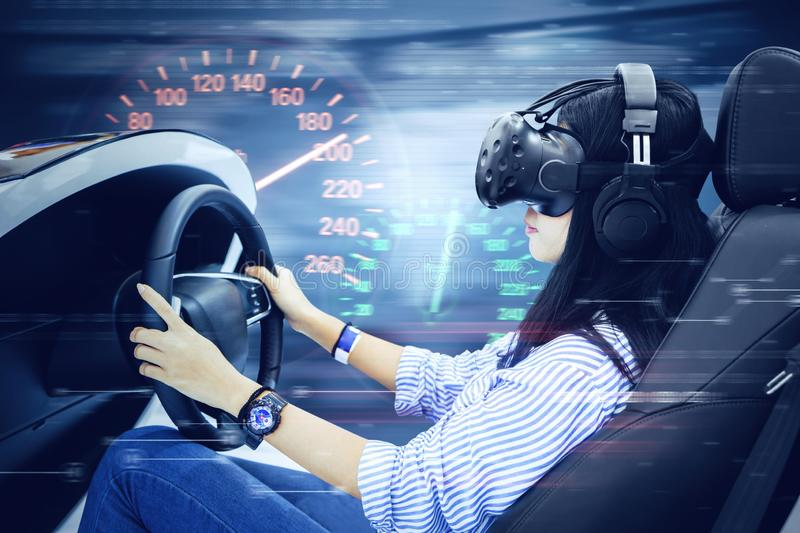 Young woman driving a virtual racing car royalty free stock photography