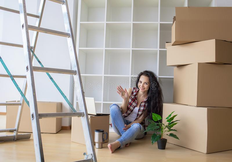 Young woman dropping cardboard box. Moving into new home royalty free stock photography