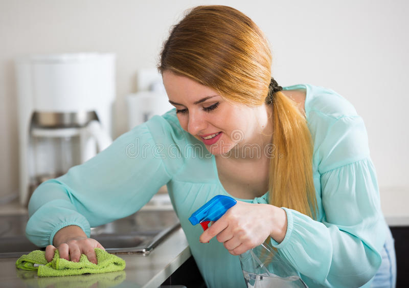 Young woman dusting kitchen tops indoors. Happy young long-haired woman cleaning kitchen tops at home stock images