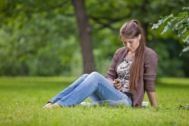 Young woman with earphones in the park. royalty free stock photo