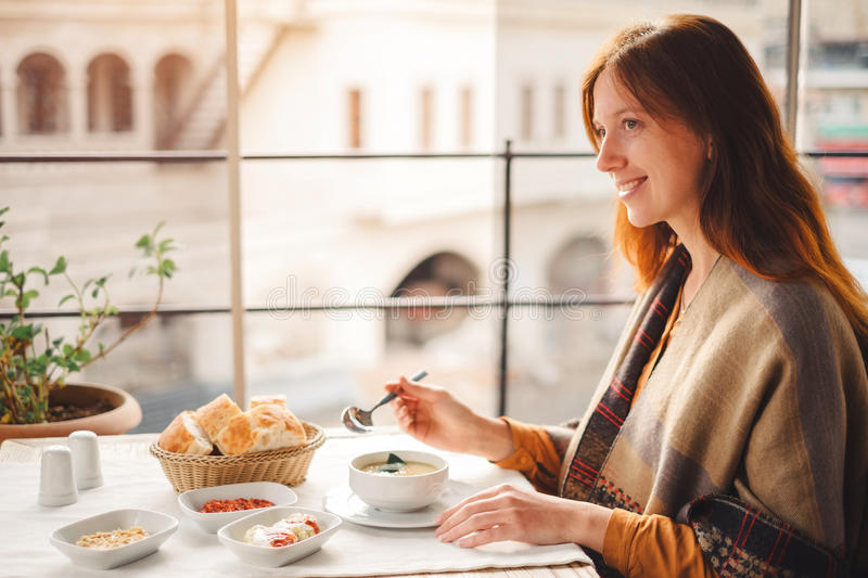 Young woman eat traditional turkish food from lentil soup. Young woman eat and enjoy tasty traditional turkish food from lentil soup stock image