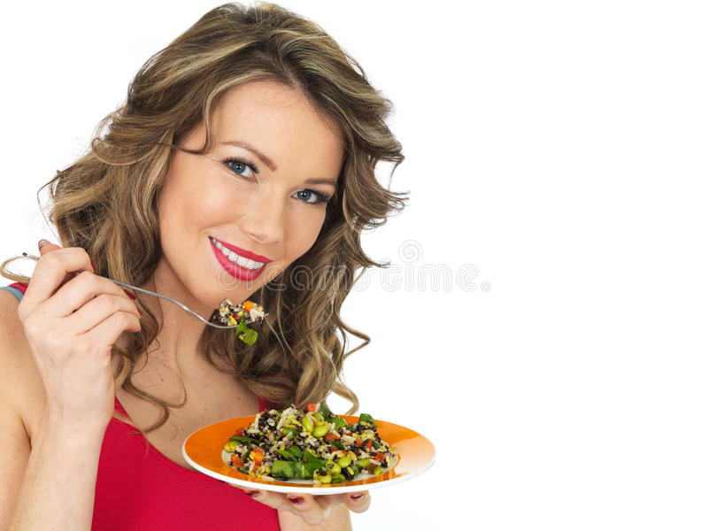 Young Woman Eating an Aromatic Rainbow Asian Style Salad. A DSLR royalty free image of an attractive young woman with dark blonde hair, eating an aromatic stock images