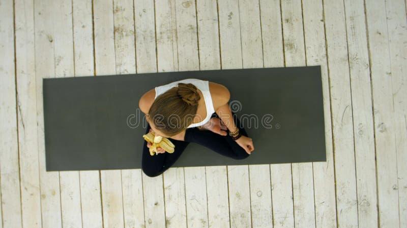 Young woman eating banana after yoga class stock photos