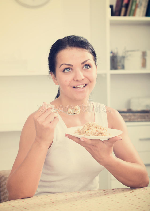 Young woman eating breakfast. Young brunette woman at home eating breakfast cereal stock photos