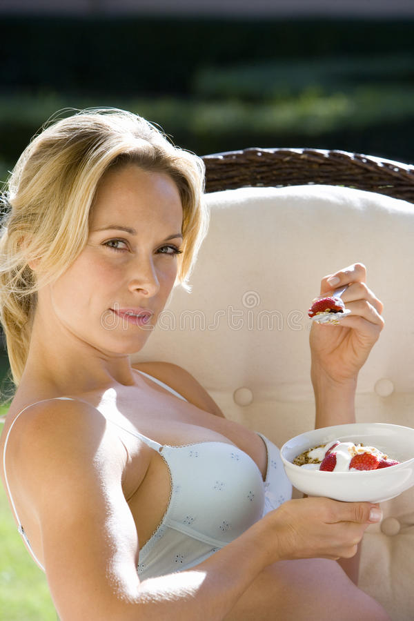 Young woman eating breakfast in underwear outdoors, portrait, close-up stock images