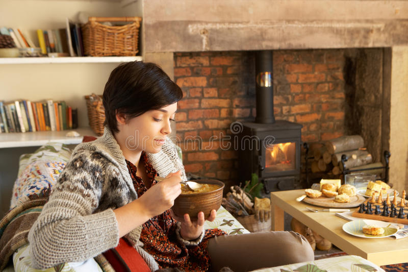 Young woman eating dinner by fire royalty free stock photography