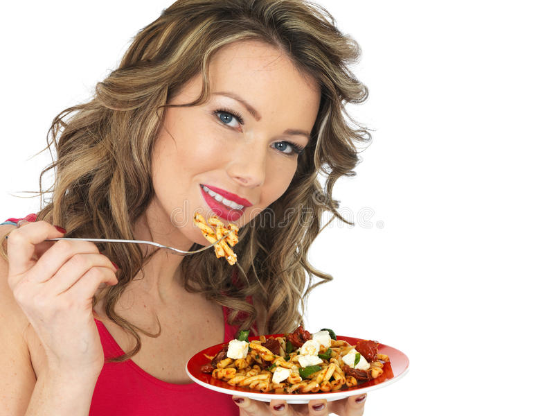 Young Woman Eating a Feta Cheese and Tomato Pasta Salad. A DSLR royalty free image of an attractive young woman with dark blonde hair, eating a plate of feta royalty free stock photo