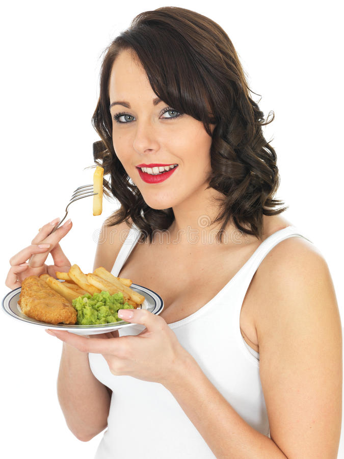 Young Woman Eating Fish and Chips. A DSLR royalty free image, happy young woman smiling, with dark hair, holding a fork with a potato chip ready to eat with a stock photos