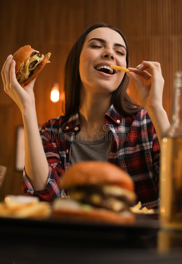 Young woman eating French fries and tasty burger. In cafe stock photography