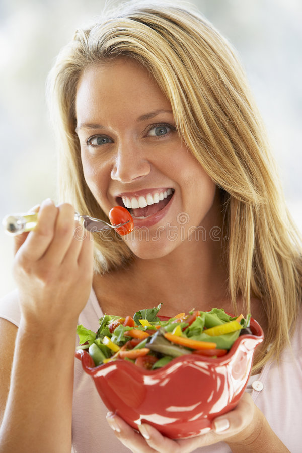 Young Woman Eating Fresh Salad royalty free stock image