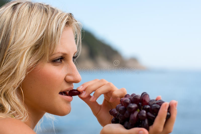 Young woman eating grapes. At the beach by the sea stock images