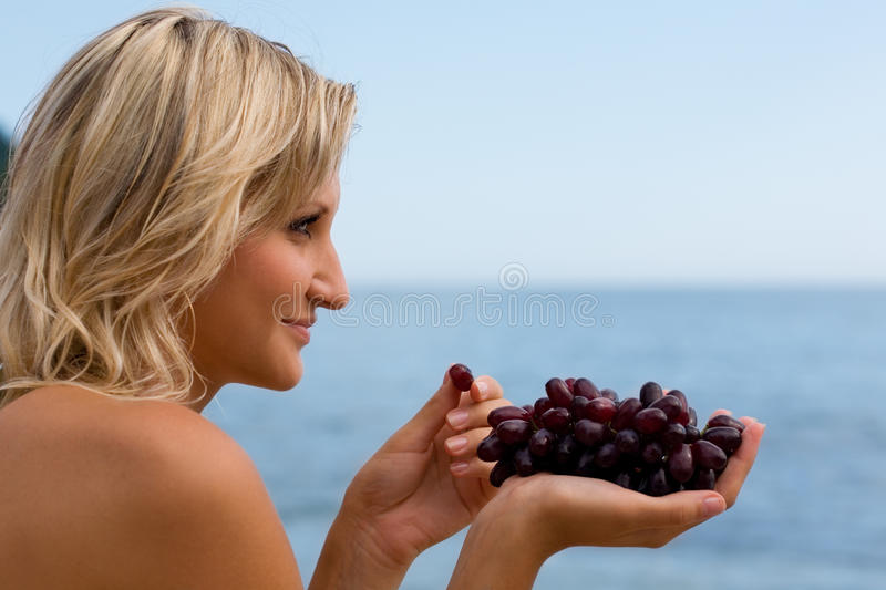 Young woman eating grapes. At the beach by the sea royalty free stock photography