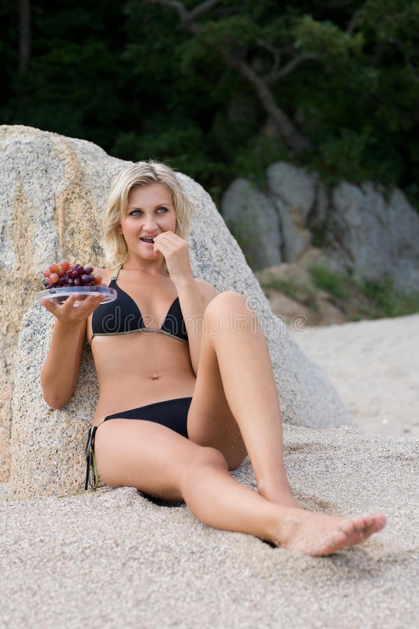 Young woman eating grapes. At the beach by the sea stock photography