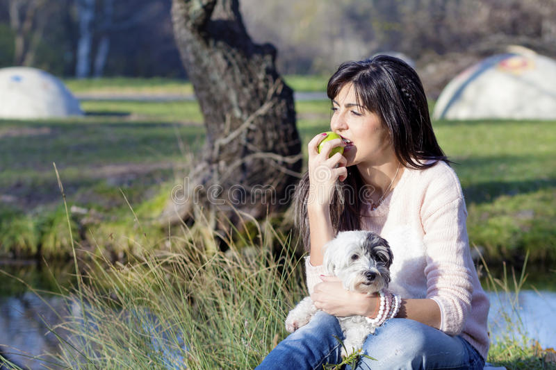 Young woman eating green apple and hugging her white dog in the park royalty free stock photo