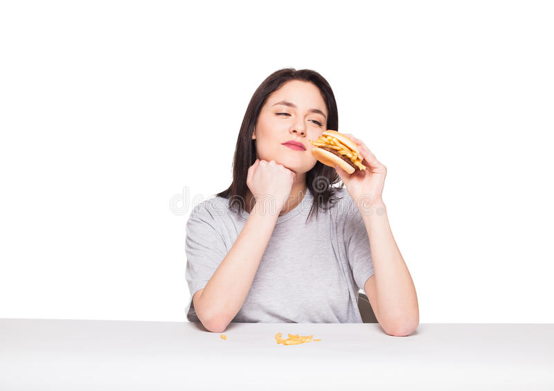 Young woman eating hamburger isolated on white. Young natural woman eating junk food, hamburger and fries, on white background royalty free stock photo