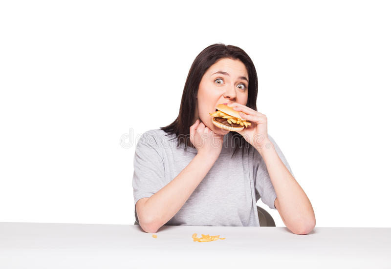 Young woman eating hamburger isolated on white. Young natural woman eating junk food, hamburger and fries, on white background stock photos