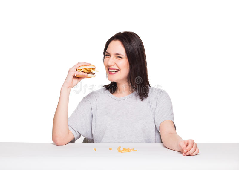 Young woman eating hamburger isolated on white. Young natural woman eating junk food, hamburger and fries, on white background royalty free stock image