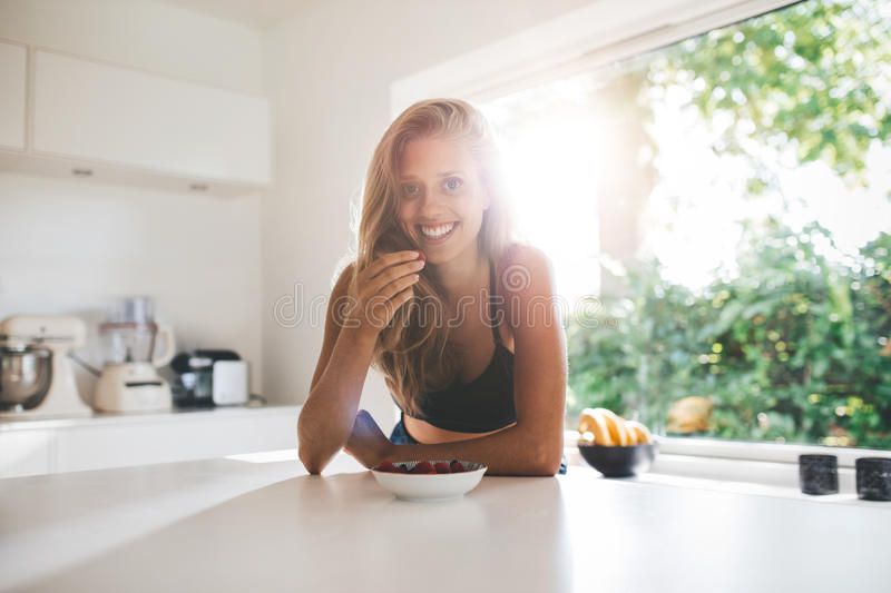 Young woman eating healthy breakfast. Portrait of young woman eating healthy breakfast in morning. Beautiful young woman in kitchen eating berries royalty free stock images