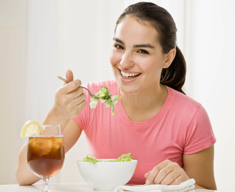 Young woman eating healthy salad stock image