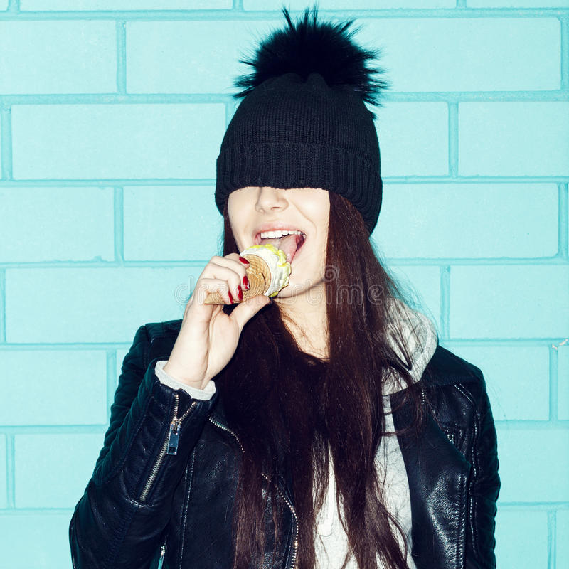 Young woman eating ice cream over blue brick wal royalty free stock image