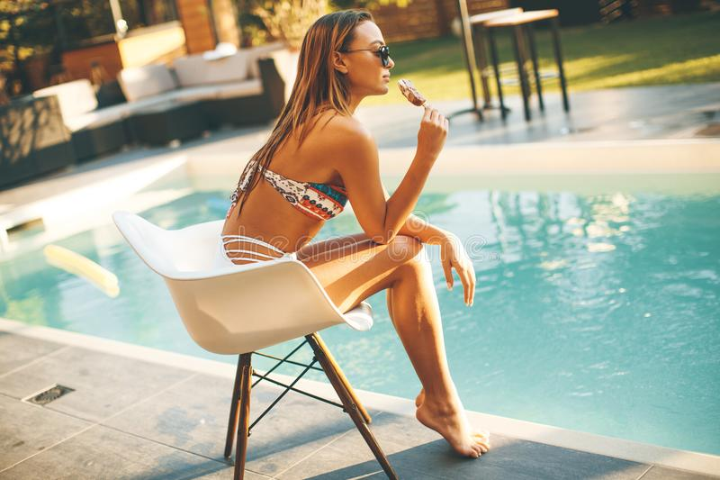 Young woman eating icecream near the swimming pool royalty free stock photos