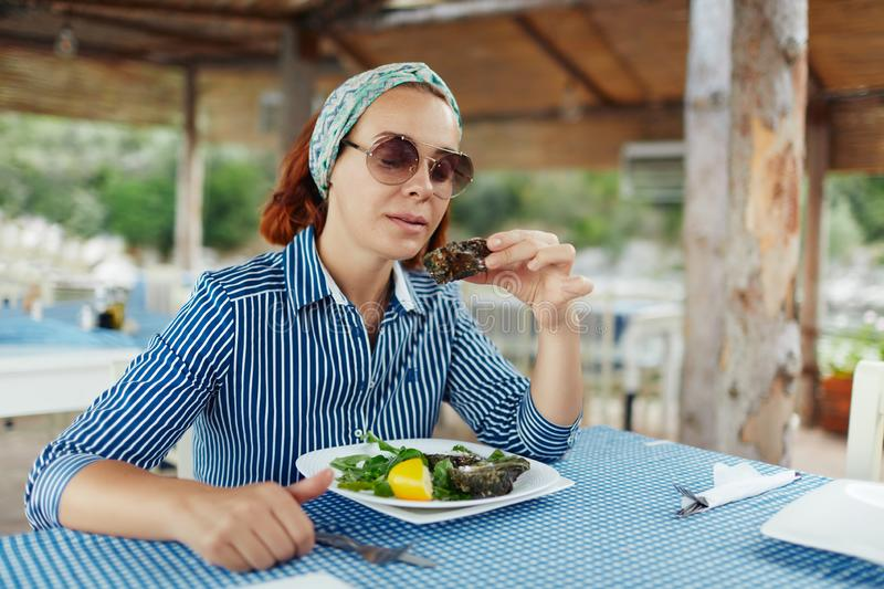 Young woman eating oyster in an outdoor restaurant royalty free stock photography